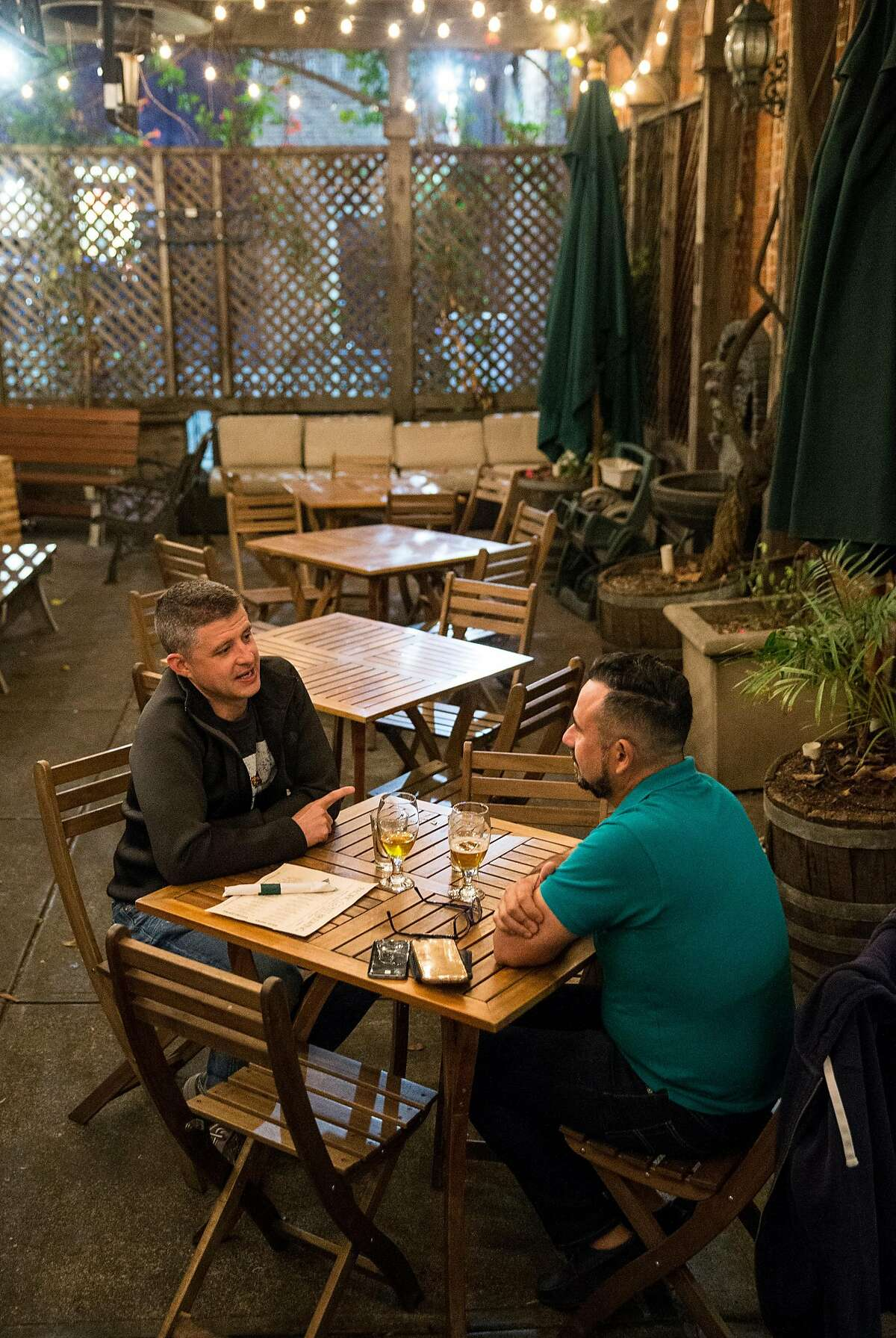 Mike Drusano (left) and German Vivanco have a drink in the outdoor backyard beer garden at Pacific Coast Brewing in Oakland, Calif., on Friday, June 2, 2017. The brewery, restaurant and bar has over 20 beers on tap including both their own brews and guest beers.