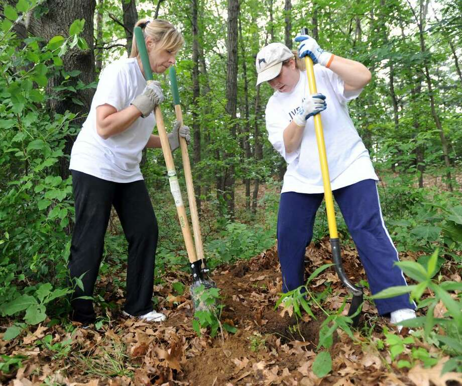 Judy Pastore, of Bethel, left, and Beverly Thulin, of Watertown, dig holes in the ground for signposts that will be placed on the children's trail at Mackauer Park in Bethel Wednesday. They were part of a group of employees of Boehringer Ingelheim that were taking part in the United Way's 16th annual Day of Caring, Wednesday, June 9, 2010. Photo: Carol Kaliff / The News-Times