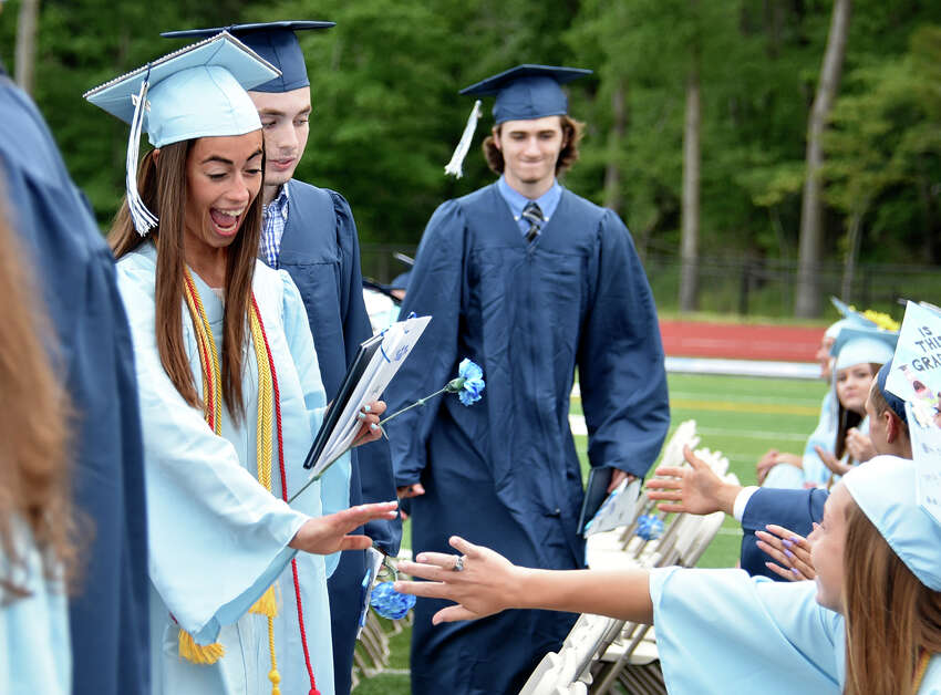 Marisa Bruno high fives a fellow graduate after receiving her diploma at the Oxford High School commencement ceremony in Oxford, Conn. on Thursday, June 15, 2017.