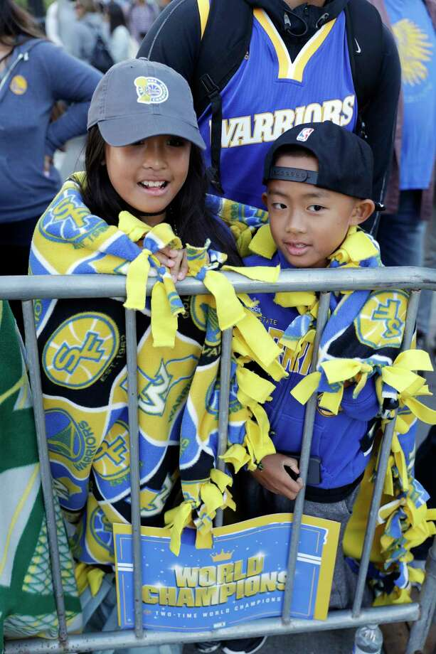 Makayla Ranola, left, and her brother Devyn wrap themselves in blankets as they wait for a parade and rally to start in honor of the Golden State Warriors, Thursday, June 15, 2017, in Oakland, Calif., to celebrate the team's NBA basketball championship. (AP Photo/Marcio Jose Sanchez) ORG XMIT: CAMS102 Photo: Marcio Jose Sanchez / Copyright 2017 The Associated Press. All rights reserved.