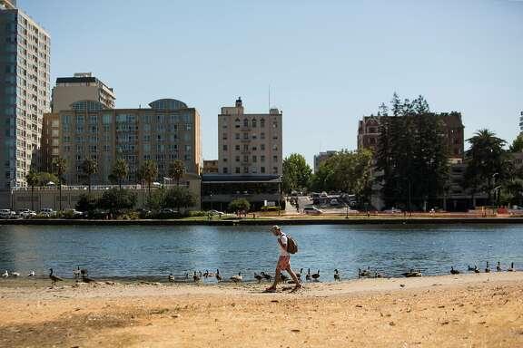 A man walks along the shore of Lake Merritt in Oakland, Calif., on Sunday, June 4, 2017.