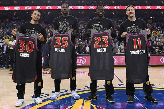 OAKLAND, CA - FEBRUARY 15:  (L-R) Stephen Curry #30, Kevin Durant #35, Draymond Green #23 and Klay Thompson #11 of the Golden State Warriors display the AllStar Jerseys prior to the start of an NBA Basketball game against the Sacramento Kings at ORACLE Arena on February 15, 2017 in Oakland, California. NOTE TO USER: User expressly acknowledges and agrees that, by downloading and or using this photograph, User is consenting to the terms and conditions of the Getty Images License Agreement.  (Photo by Thearon W. Henderson/Getty Images)