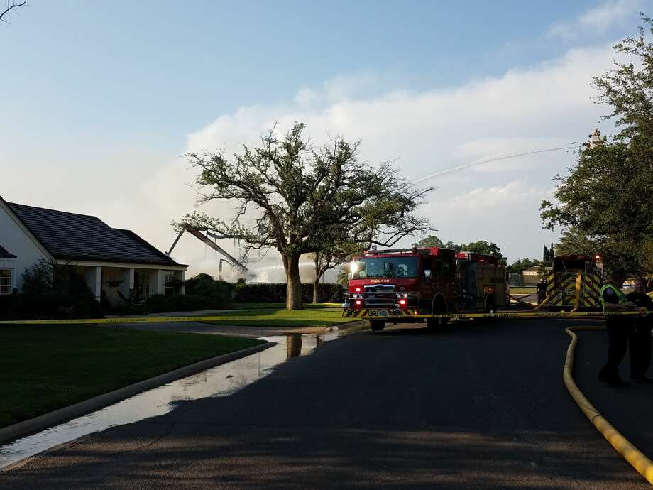 Midland firefighters continue to put water on hot spots Thursday evening after a fire destroyed a home under construction on Racquet Club Drive. Photo: Mercedes Cordero/Reporter-Telegram