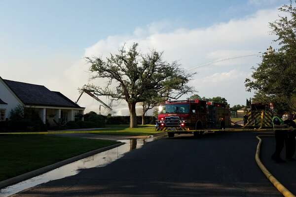 Midland firefighters continue to put water on hot spots Thursday evening after a fire destroyed a home under construction on Racquet Club Drive.