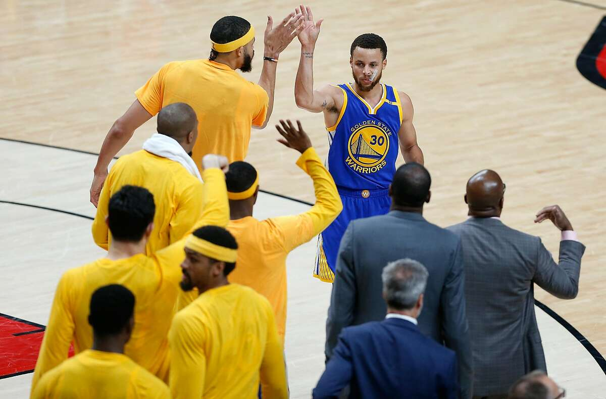 PORTLAND, OR - APRIL 22: Stephen Curry #30 of the Golden State Warriors high fives teammates on the bench against the Portland Trail Blazers during Game Three of the Western Conference Quarterfinals of the 2017 NBA Playoffs at Moda Center on April 22, 2017 in Portland, Oregon. NOTE TO USER: User expressly acknowledges and agrees that, by downloading and or using this photograph, User is consenting to the terms and conditions of the Getty Images License Agreement. (Photo by Jonathan Ferrey/Getty Images)