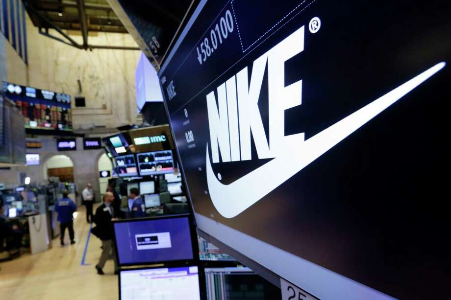 FILE - In this Wednesday, March 22, 2017, file photo, the Nike logo appears above the post where it trades on the floor of the New York Stock Exchange. On Thursday, June 15, 2017, Nike said it plans to cut about 1,400 jobs, reduce the number of sneaker styles it offers by a quarter and sell more shoes directly to customers online. The company says the changes to its business structure will help it offer more products to customers faster. (AP Photo/Richard Drew, File) ORG XMIT: NYBZ431 Photo: Richard Drew / AP