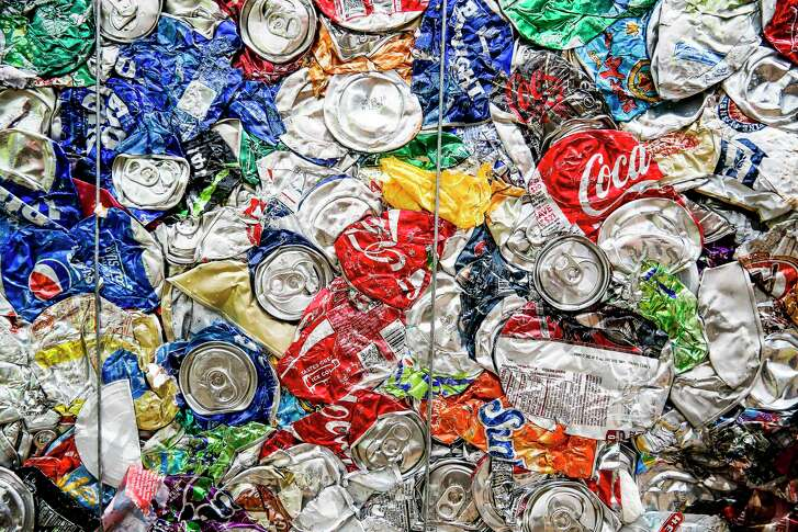 Crushed cans wait for recycling at a Waste Manage- ment site. Prices for recycling can be unpredictable.