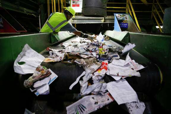 A Waste Management employee sorts through paper at the Gasmer Recycling Center Friday, June 2, 2017 in Houston. ( Michael Ciaglo / Houston Chronicle )
