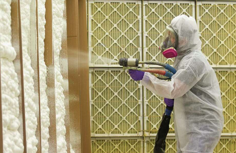 A Huntsman employee demonstrated a spray foam that uses chemicals created by Huntsman during a tour of the company's operation in The Woodlands Tuesday, Oct. 25, 2016. Photo: Jason Fochtman, Staff Photographer / Houston Chronicle