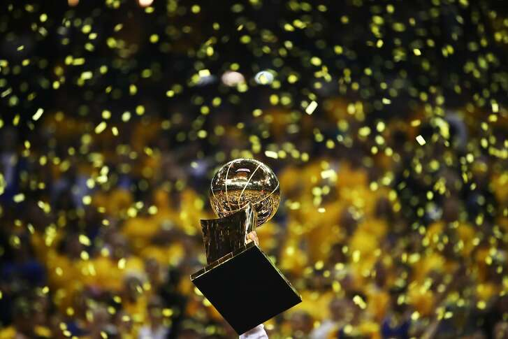 OAKLAND, CA - JUNE 12: The Larry O'Brien Championship Trophy is held up by the Golden State Warriors after the defeated the Cleveland Cavaliers 129-120 in Game 5 to win the 2017 NBA Finals at ORACLE Arena on June 12, 2017 in Oakland, California. NOTE TO USER: User expressly acknowledges and agrees that, by downloading and or using this photograph, User is consenting to the terms and conditions of the Getty Images License Agreement.  (Photo by Ezra Shaw/Getty Images)