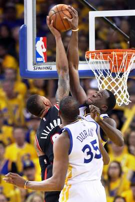 Golden State Warriors' Draymond Green blocks a dunk attempt by Portland Trail Blazers' Damian Lillard as Kevin Durant watches in 4th quarter during Warriors' 121-109 win in Game 1 of NBA Western Conference 1st Round Playoffs at Oracle Arena in Oakland, Calif., on Sunday, April 16, 2017.