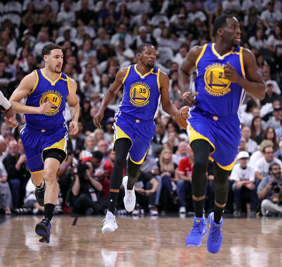 Golden State Warriors' Kevin Durant brings the ball up court flanked by Klay Thompson and Draymond Green in 1st quarter against San Antonio Spurs'during Game 3 of NBA Western Conference Finals at AT&T Center in San Antonio, Texas, on Saturday, May 20, 2017.