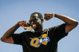 Golden State Warriors'  Draymond Green flexes his muscles during the championship parade in Oakland, Calif., on Thursday, June 15, 2017.