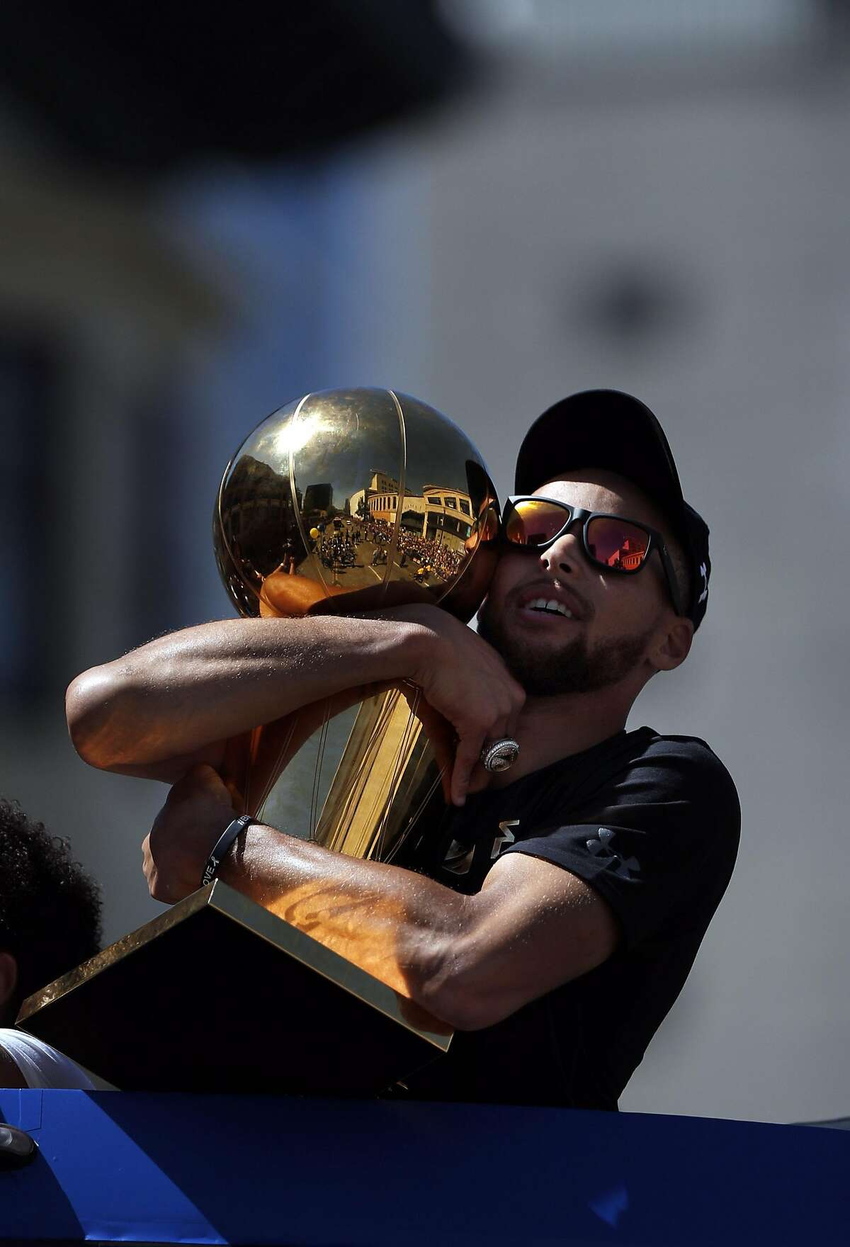 Stephen Curry hugs the Larry O'Brien Trophy as the Golden State Warriors celebrated their NBA Championship with a victory parade in Oakland, Calif., on Thursday, June 15, 2017.