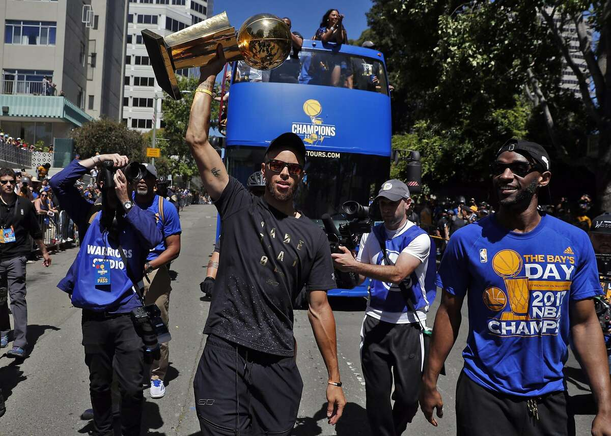 Stephen Curry and Ian Clark carry the Larry O'Brien Trophy along the route as the Golden State Warriors celebrated their NBA Championship with a victory parade in Oakland, Calif., on Thursday, June 15, 2017.