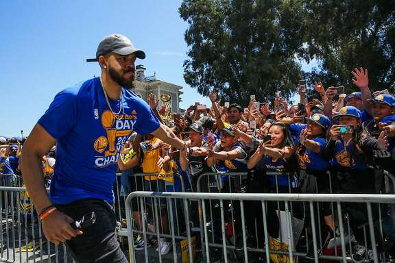 Golden State Warriors' JaVale McGee high-fives fans during the championship parade in Oakland, Calif., on Thursday, June 15, 2017.
