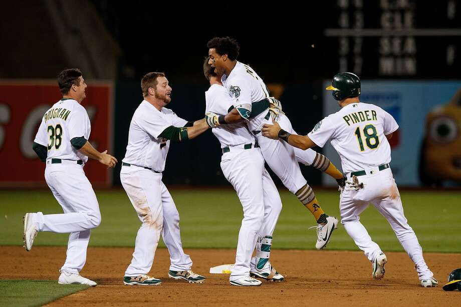 Khris Davis of the Oakland Athletics celebrates with teammates after hitting a walk off two run single during the tenth inning against the New York Yankees at the Oakland Coliseum on June 15, 2017 in Oakland, California. The Oakland Athletics defeated the New York Yankees 8-7 in 10 innings. Photo: Jason O. Watson, Getty Images