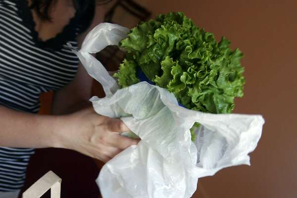Lettuce, along with several other items, arrives in an individual plastic bag within the paper bags delivered by Amazon Fresh to a residence on Mercer Island, Wash., Thursday, Aug. 23, 2007. Amazon Fresh is a new grocery delivery service being tested by Amazon.com in a handful of Seattle neighborhoods including Mercer Island. Amazon.com has deployed a fleet of 12 grocery delivery trucks. Customers can also pick up fresh grocery orders at a small number of locations in the area. (AP Photo/Joe Nicholson)