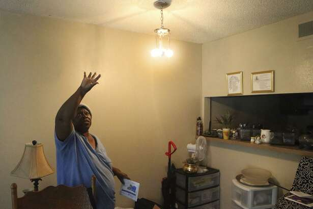 Hellene Hunt gestures toward the ceiling that she said would leak whenever there was a rainstorm. It took the management of her apartment complex, Avistar at Chase Hill, more than a year to fix the leaks, she said.