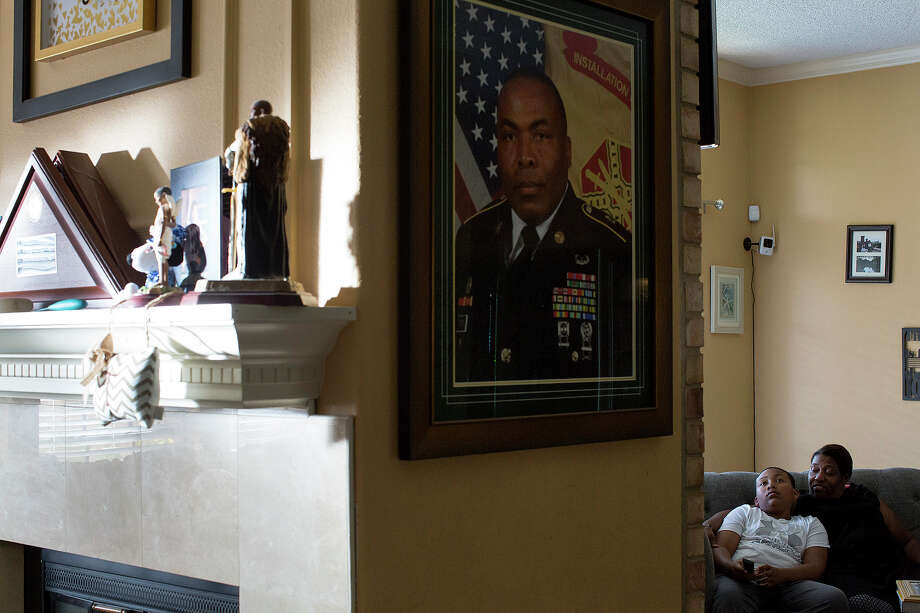 Katherine Turner and her son, Xavier Turner, 12, watch television at home near a portrait of her husband and Xavier's father, Sgt. Maj. Wardell Turner, on March 19, 2017.