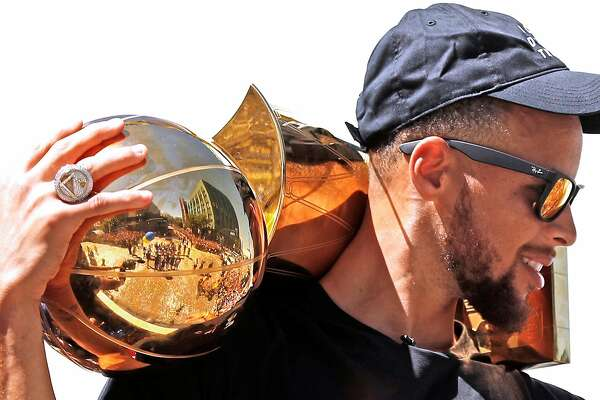 Golden State Warriors' Stephen Curry holds the Larry O'Brien trophy during championship parade on Broadway in Oakland, Calif., on Thursday, June 15, 2017.