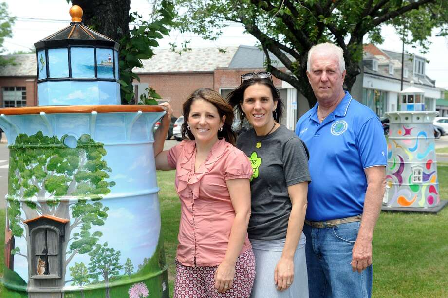 """Aubrey Booska and Michelle Genuario, co-chairs of the Stratford Street Sculpture Committee, and Rich Fredette, chairman of the Stratford Arts Commission, stand with one of the twenty decorated """"Light the Way"""" lighthouses that are now on display along Main Street in Stratford, Conn. June 15, 2017. Photo: Ned Gerard / Hearst Connecticut Media / Connecticut Post"""