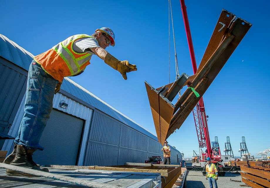 Steel beams, above, from the Bay Bridge — 33 tons of them — are loaded onto a truck for artist Katy Boynton, below, who will remove the rust, paint it gray and install it at Pier 3 in S.F. to separate a parking lot from a pedestrian walkway. Photo: John Storey, Special To The Chronicle