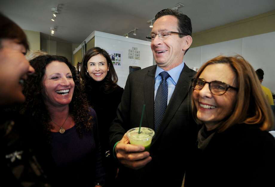 Governor Dannel P. Malloy samples a juice drink with Tara Cook-Littman, second from left, after a ceremonial bill signing of Public Act 13-183, that requires the labeling of genetically engineered foods, at Catch a Healthy Habit Cafe at 39 Unquowa Road in Fairfield, Conn. on Wednesday, December 12, 2013. Cook-Littman, of GMO Free CT, has been the driving force championing the GMO labeling law in the legislature. Photo: Brian A. Pounds / Brian A. Pounds / Connecticut Post