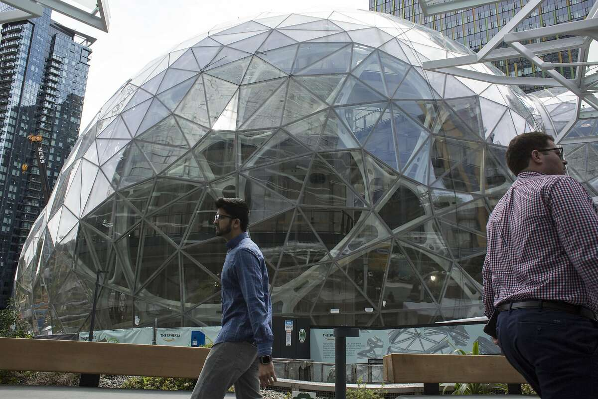 People walk past the signature glass spheres under construction at the Amazon corporate headquarters on June 16, 2017 in Seattle, Washington. Amazon announced that it will buy Whole Foods Market, Inc. for over $13 billion.