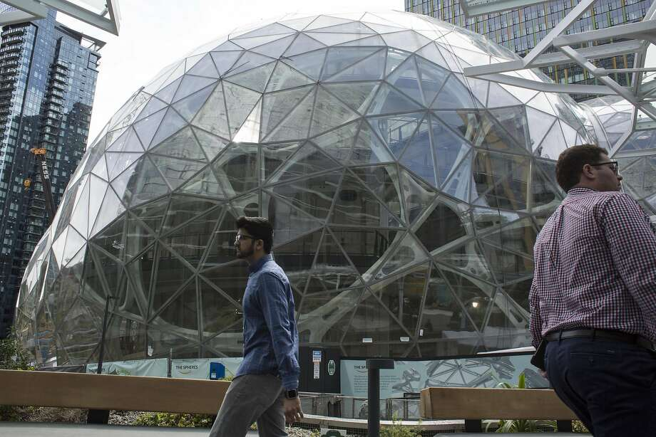 SEATTLE, WA - JUNE 16: People walk past the signature glass spheres under construction at the Amazon corporate headquarters on June 16, 2017 in Seattle, Washington. Amazon announced that it will buy Whole Foods Market, Inc. for over $13 billion.  (Photo by David Ryder/Getty Images) Photo: David Ryder, Getty Images