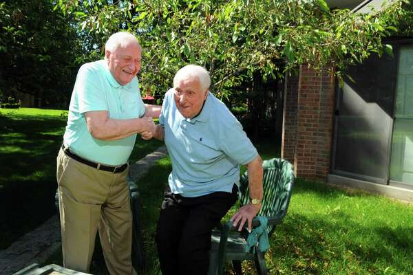 Ninety-five-year-old Sal Maniscalco, left, helps up his twin brother Tom as they hang out together at Sal's condo in Fairfield, Conn., on Wednesday June 14, 2017.