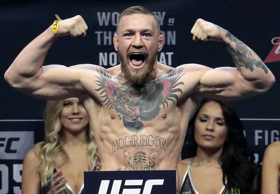 FILE - In this Nov. 11, 2016, file photo, Conor McGregor stands on a scale during the weigh-in event for his fight against Eddie Alvarez in UFC 205 mixed martial arts at Madison Square Garden in New York. Boxer Floyd Mayweather Jr. said Wednesday, June 14, 2017,  he will come out of retirement to face UFC star Conor McGregor in a boxing match on Aug. 26. Mayweather, who retired in September 2015 after winning all 49 of his pro fights, will face a mixed martial arts fighter who has never been in a scheduled 12-round fight at the MGM Grand arena. The fight will take place in a boxing ring and be governed by boxing rules. (AP Photo/Julio Cortez, File) Photo: Julio Cortez / Associated Press