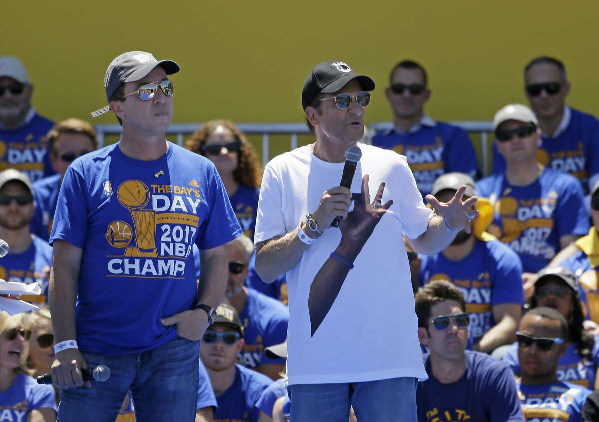Team owners Joe Lacob, left, and Peter Guber, right, speak during the Golden State Warriors NBA championship rally Thursday, June 15, 2017, in Oakland, Calif. Oakland is celebrating its second championship in the past three years. (AP Photo/Eric Risberg)