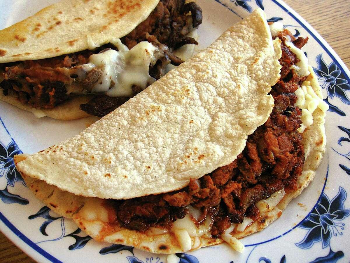 Al pastor pirata taco on a handmade corn tortilla, foreground, and a beef fajita pirata taco on flour from Santos Cafe #1.