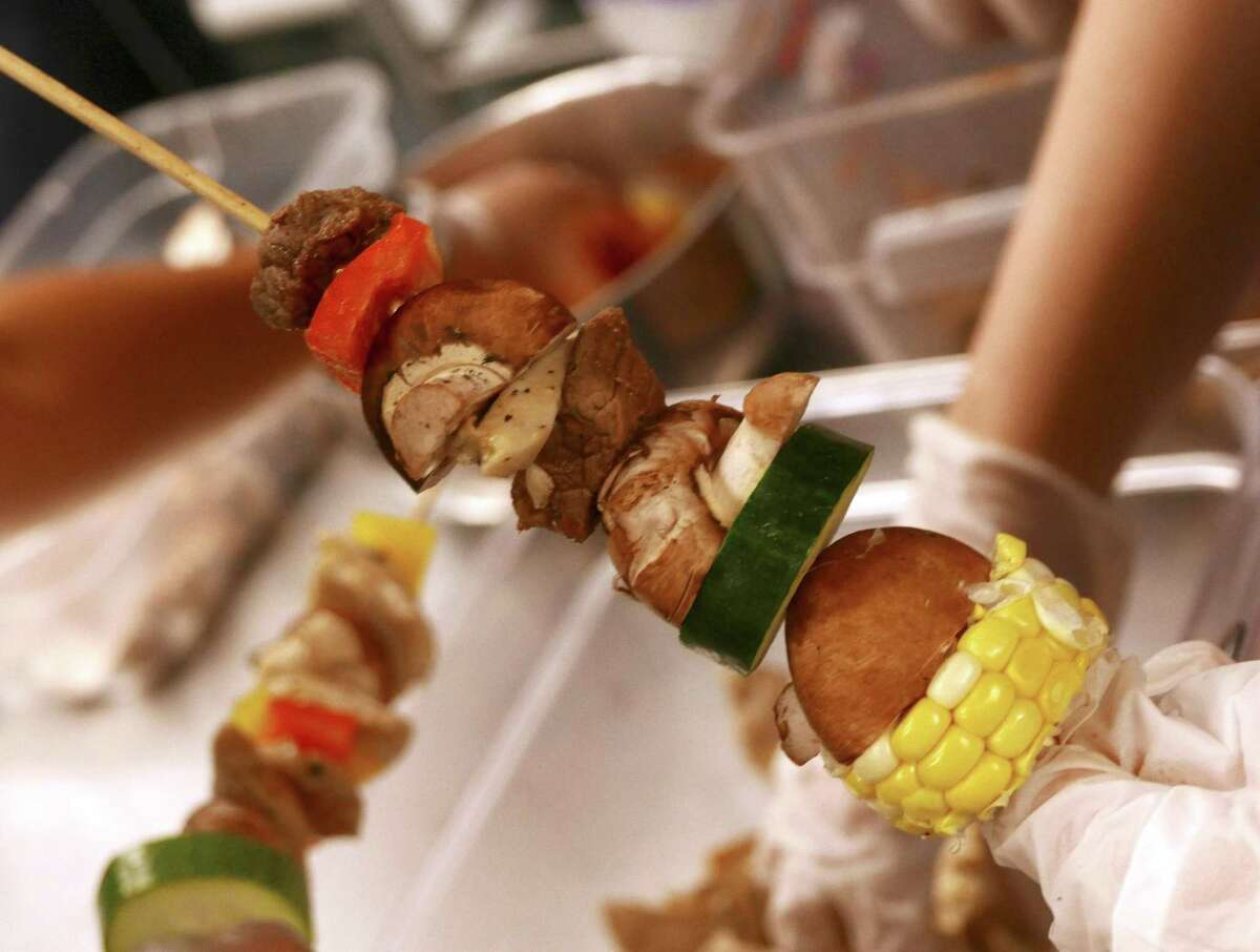 People with autism prepare kabobs at the San Antonio Clubhouse on Wednesday, June 14, 2017. Trinity University and the Spectrum Community nonprofit are having a week of classes to teach autistic people how to be independent and prepare them for college.