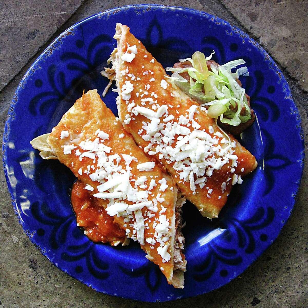 A rolled taco entomatado with chicken in a handmade tortilla from La Siberia Taquería.