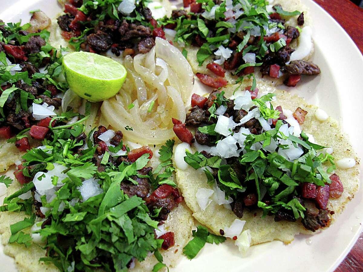 Pirata mini-tacos with beef, sausage, bacon, mozzarella cheese, onions and cilantro on handmade corn tortillas from La Siberia Taquería.