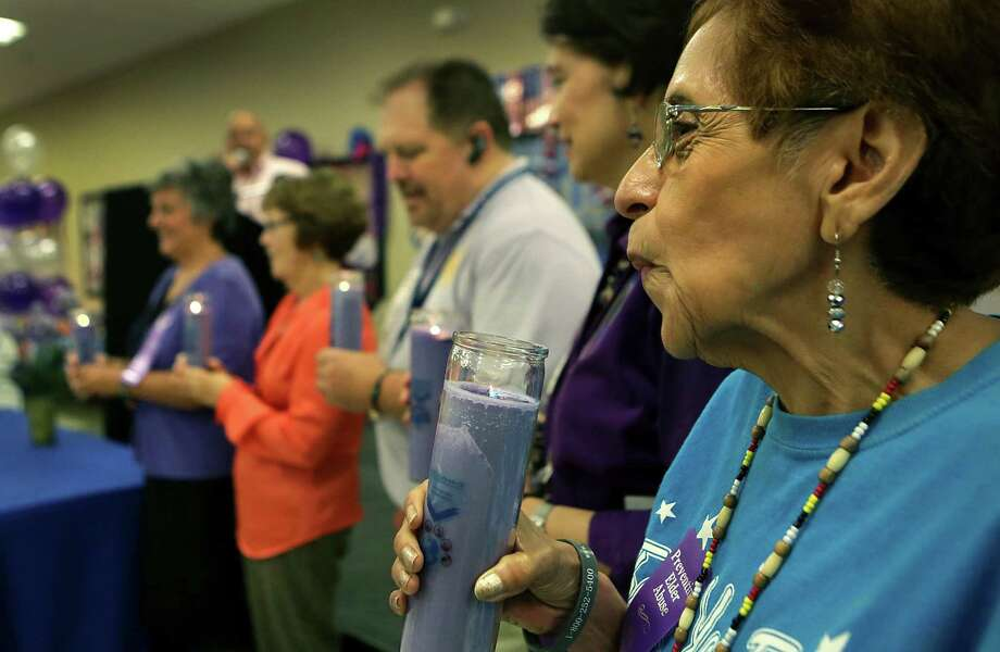Rallying to end elder abuse, Noemi Carreon, right, blows out a purple candle with others at at the Elvira Cisneros Senior Community Center in 2015. Photo: Bob Owen /San Antonio Express-News / San Antonio Express-News