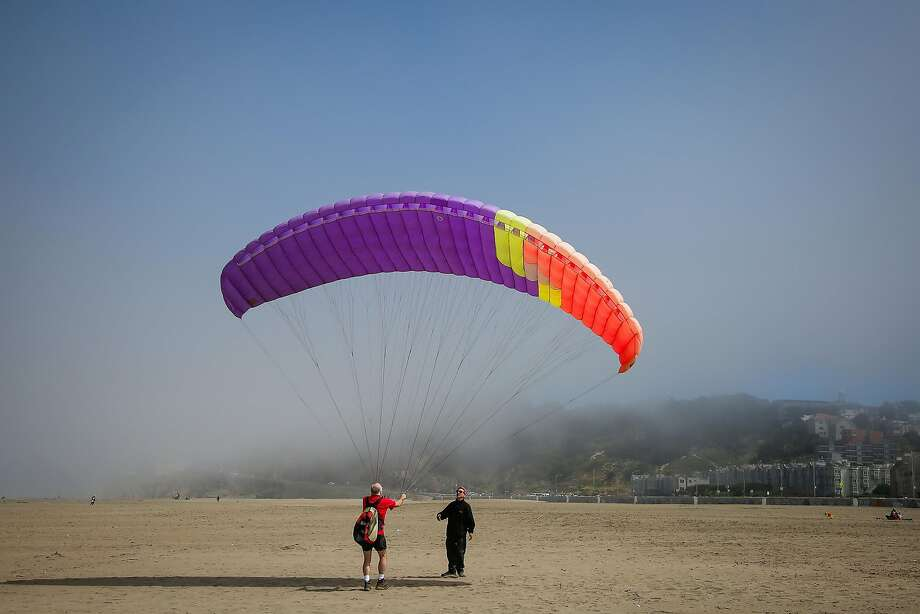 Paragliding instructor Jeff Greenbaum teaches a friend how to paraglide on Ocean Beach in San Francisco on June 13, 2017. Greenbaum says serious accidents rarely happen in the sport. On Wednesday, an Australian paraglider was prematurely launched by a violent dust devil that blew him and his wing off a cliff. He escaped unharmed. Photo: Nicole Boliaux, The Chronicle
