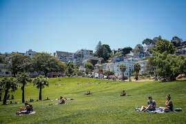 People sunbathe in Mission Dolores Park in San Francisco on Friday, June 16, 2017.