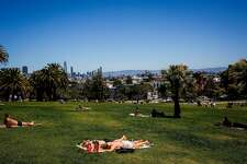 People sunbathe in Mission Dolores Park in San Francisco on June 13, 2017.