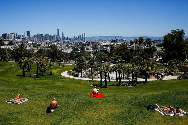 People sunbathe in Mission Dolores Park in San Francisco on June 13, 2017.