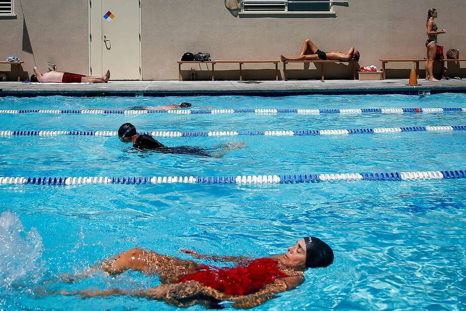 People swim and sunbathe during lap swimming at Mission Pool in San Francisco. All city pools are planned to be open and free on Saturday. Photo: Nicole Boliaux, The Chronicle
