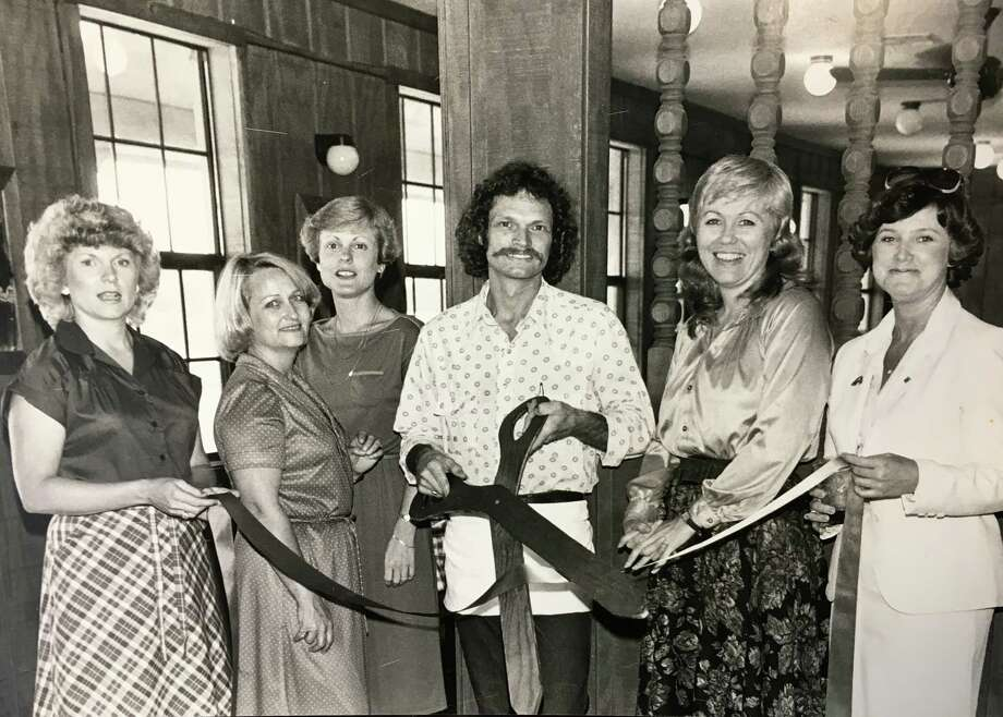 A Chamber ribbon cutting at the Old West Steakhouse on Texas 105. Chamber Embassy Club members assisting owner Michael Edwards, center, are Patty Calfee, Charline Utley, Sue Scripture, Lana Hughes and Sally Copley. Photo taken in the 1970s/80s era.