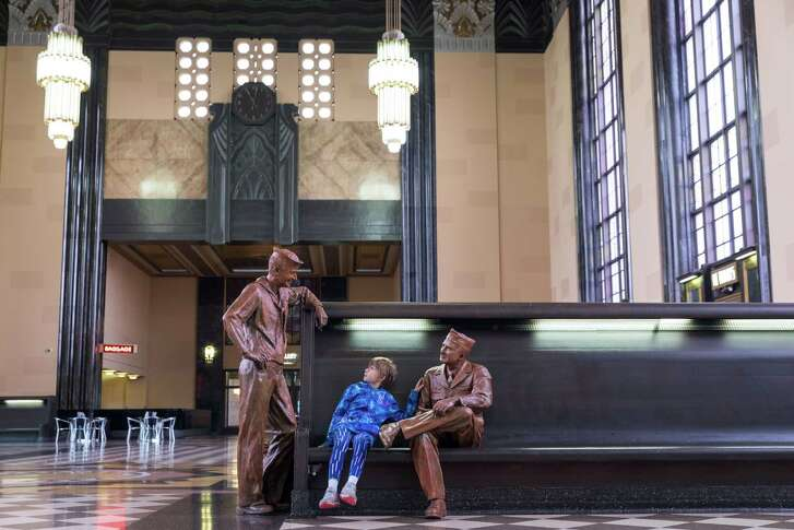 Illyana Kelley, 9, seems to be regaled by the stories of these servicemen, two of the lifelike statues placed around the Durham Museum in Omaha, in the 86-year-old confines of the former Union Station.