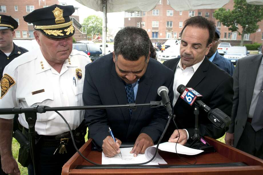 "James Slaughter, center, Interim Executive Director of the Bridgeport Housing Authority, signs a memorandum of understanding dedicating Community Policing Details to public housing sites around the City of Bridgeport, June 16, 2017. Slaughter is joined here by Police Chief Armando ""A.J."" Perez, left, and Mayor Joe Ganim. Photo: Ned Gerard / Hearst Connecticut Media / Connecticut Post"