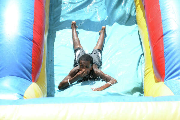 Children enjoy cooling off as they soar down the inflatable water slide during the Port Arthur Police Department's Fun Fest, held at Valley View Estates Friday. Games, bounce houses, a water slide, snacks, and raffle prizes for children were among the highlights of the event, which is part of PAPAD's initiative to create a stronger bond and good relations within the community. The department plans to hold similar events monthly throughout the summer and for as long as funds allow. They are working in conjunction with the Housing Authority to hold the festivals at housing complexes throughout the community. Photo taken Friday, June 16, 2017 Kim Brent/The Enterprise