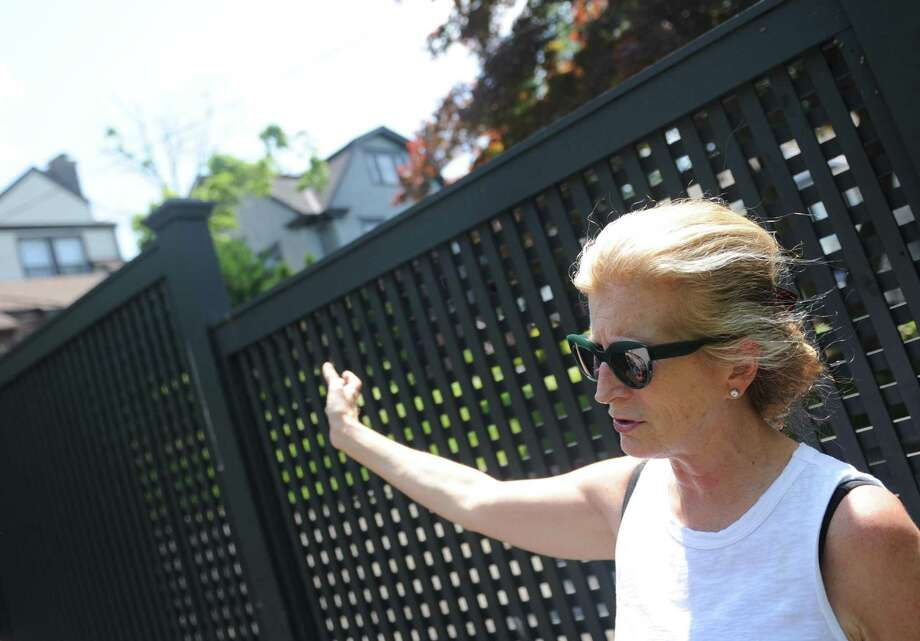 Elizabeth Newman looks over the fence to her neighbor's home, which will soon be demolished to make way for a larger multi-family home on Milbank Avenue in Greenwich, Conn. Tuesday, June 13, 2017. Photo: Tyler Sizemore / Hearst Connecticut Media / Greenwich Time