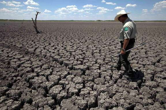 Texas State Park Police Officer Thomas Bigham examines the cracked lake bed of O.C. Fisher Lake in San Angelo in 2011. Climate change has been debated for decades.