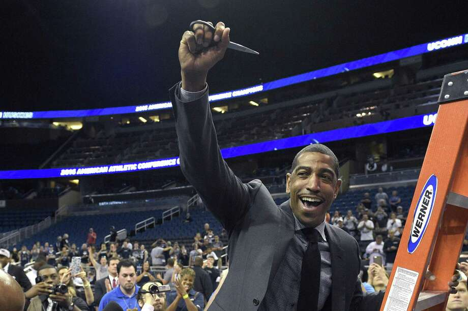 Connecticut head coach Kevin Ollie celebrates while climbing a ladder to cut down the net after an NCAA college basketball game against Memphis in the finals of the American Athletic Conference men's tournament in Orlando, Fla., Sunday, March 13, 2016. Connecticut won 72-58. (AP Photo/Phelan M. Ebenhack) Photo: Phelan M. Ebenhack / AP / FR121174 AP